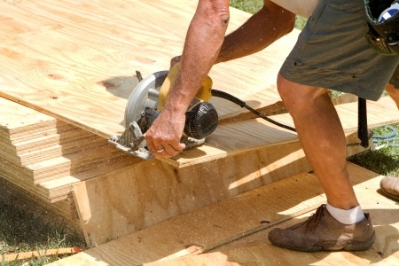 14182525 - sawdust fills the air as a carpenter uses a electric powered circular saw to cut a sheet of plywood at a construction site