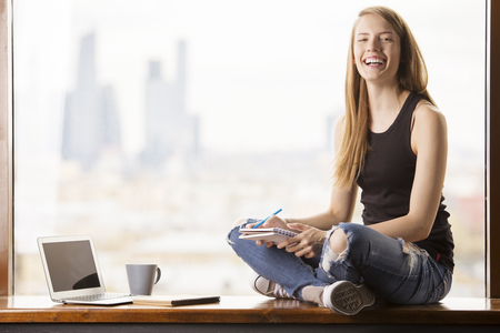 57349604 - happy young woman with notepad in hand sitting on windowsill with blank laptop screen. blurry city view in the background. mock up