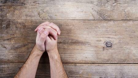 37086006 - hands of praying young man on a wooden desk background.