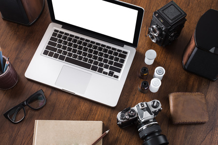43074034 - work space for photographer, designer or hipster style. have a laptop, film camera, film, speaker, glasses, book, pencil on wooden table.